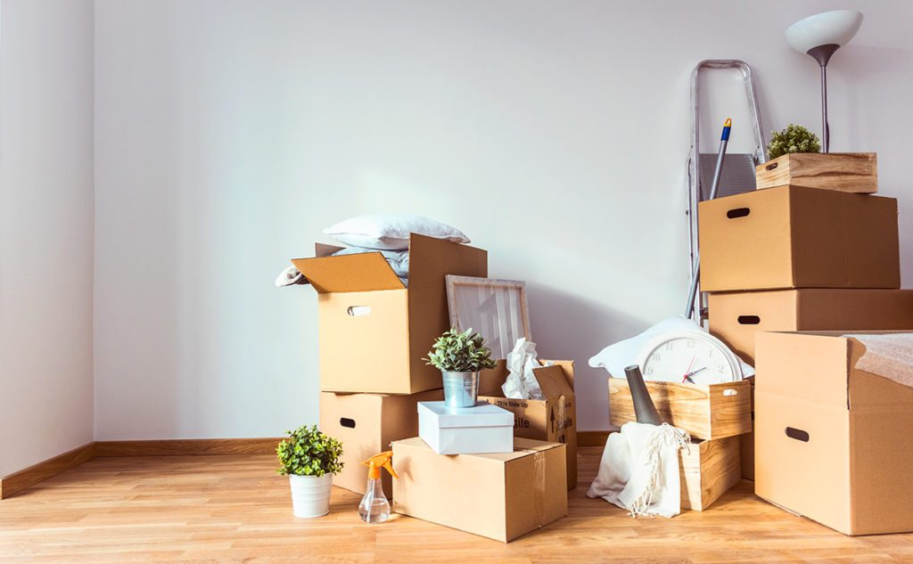 Stacks of boxes and miscellaneous items in an empty apartment with wood floors and white walls