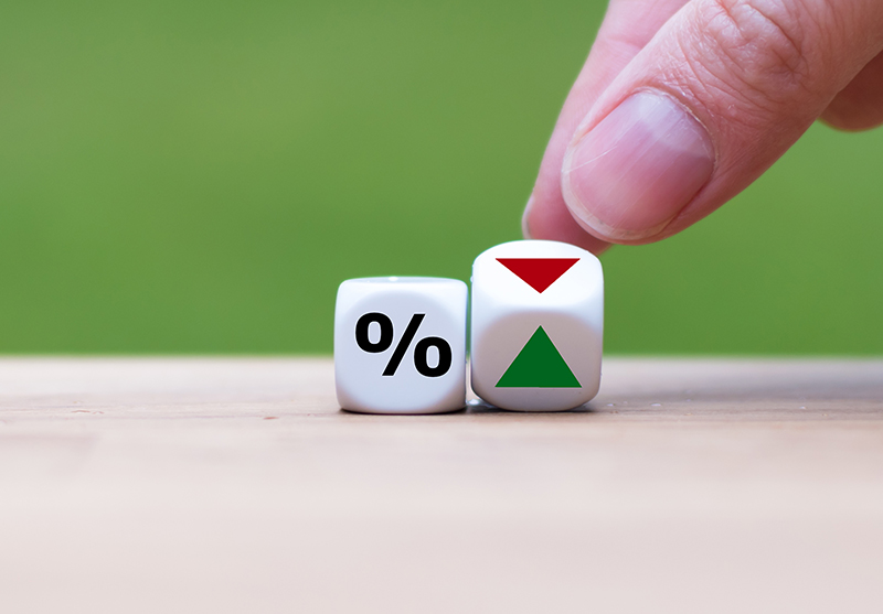 Hand grabbing at one of two dice. One die has a percentage sign and another has a green arrow facing upward and other has a downward facing red arrow.